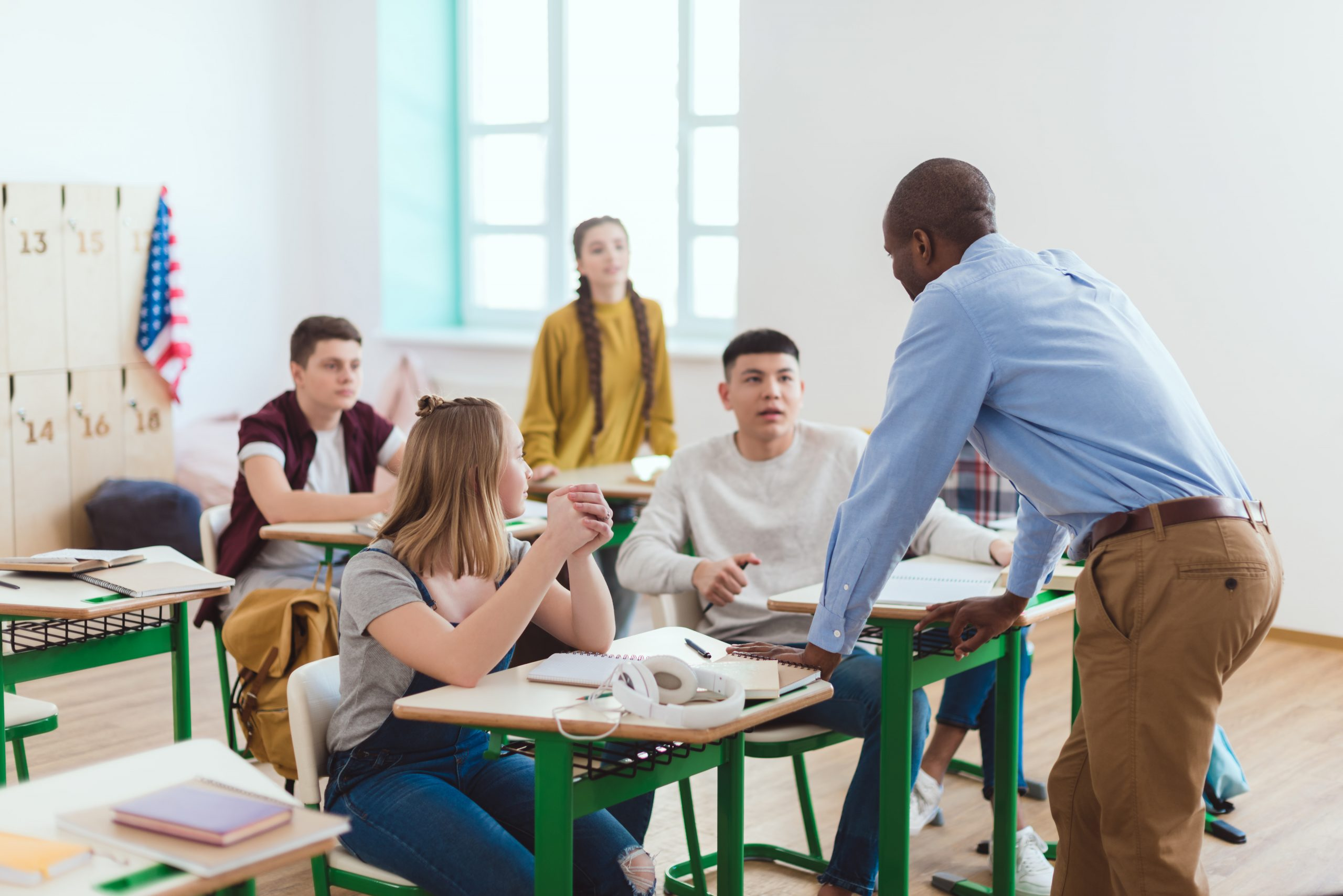Rear view of african american teacher and high school teenage students in classroom