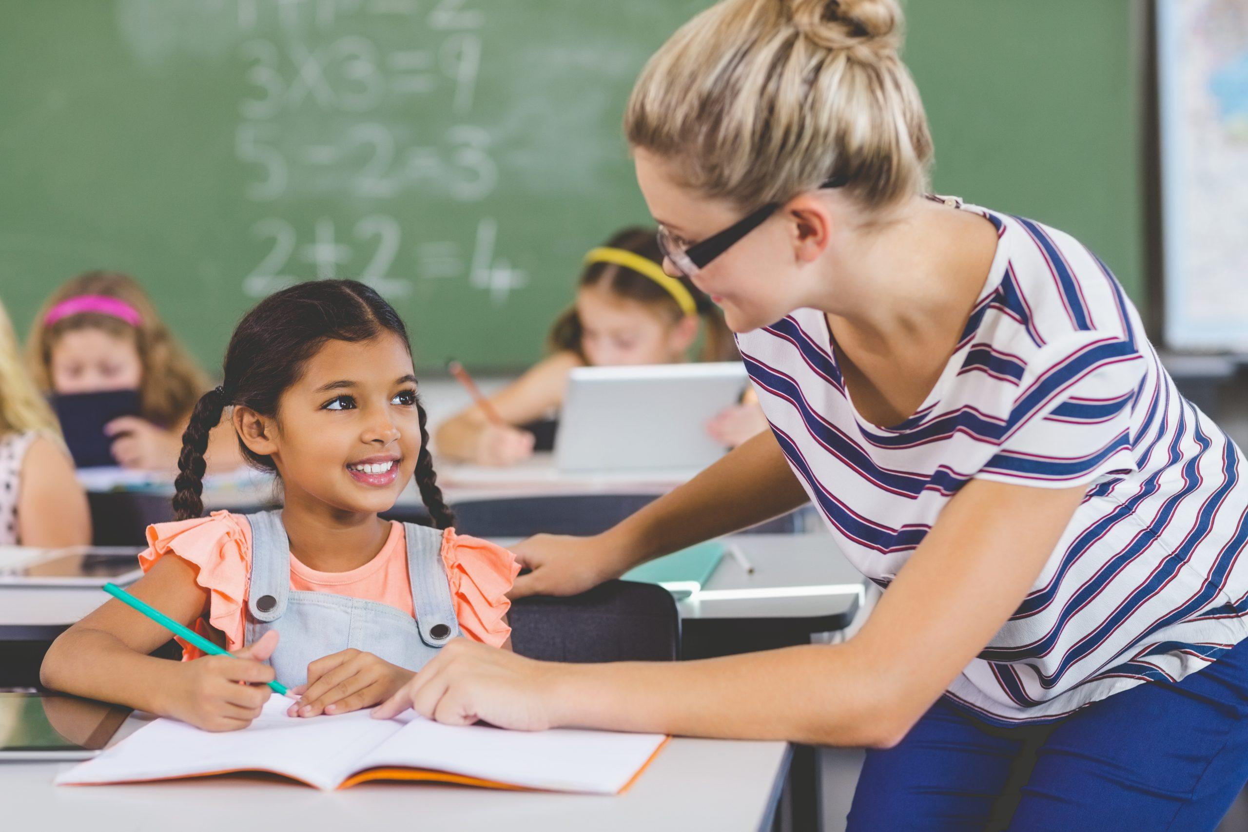 Teacher helping kids with their homework in classroom
