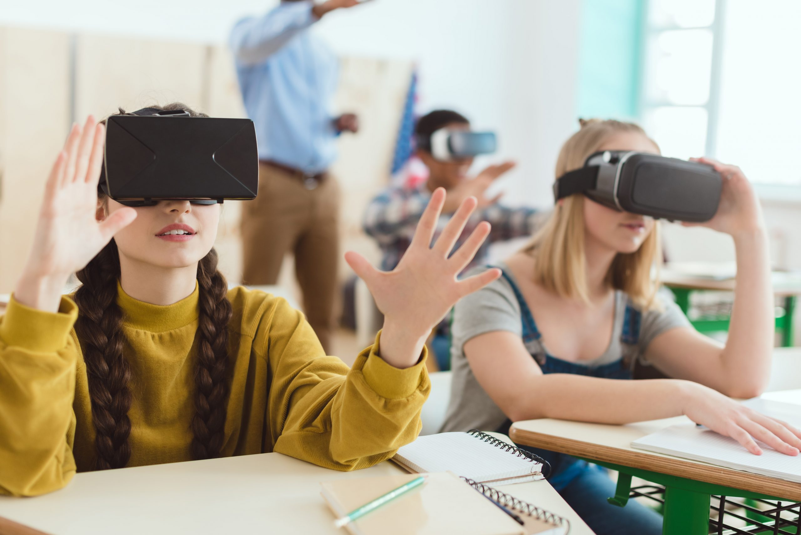 Two teenage schoolgirls using virtual reality headsets and classmate with teacher behind
